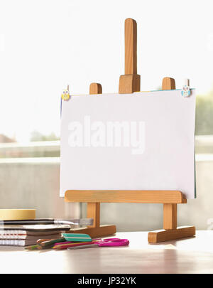 Small wooden easel with blank paper and school supplies on desk - Stock Photo