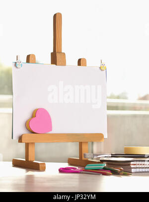 Small blank easel with heart shaped stickers and other school supplies on desk - Stock Photo