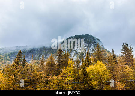 Mountain cliff by highway road with wires in stormy misty and foggy weather in mountain Charlevoix region of Quebec, - Stock Photo