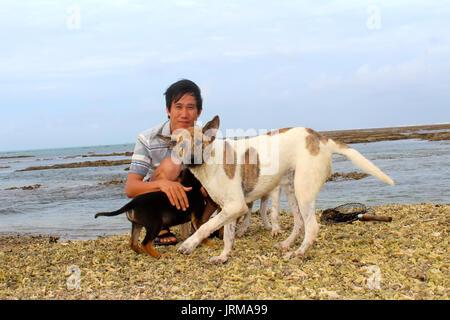 KHANH HOA, VIETNAM, September, 17: man with dog at the sea on September, 17, 2013 in Khanh Hoa, Vietnam - Stock Photo