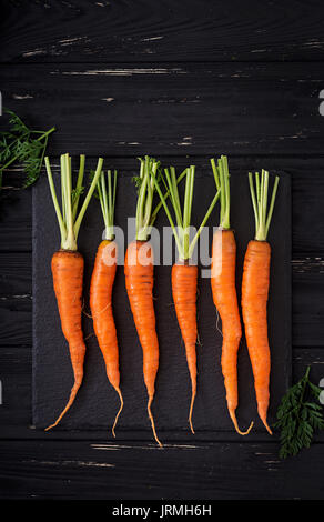 Bunch of fresh carrots with green leaves on  dark  wooden background. Flat lay. Top view - Stock Photo