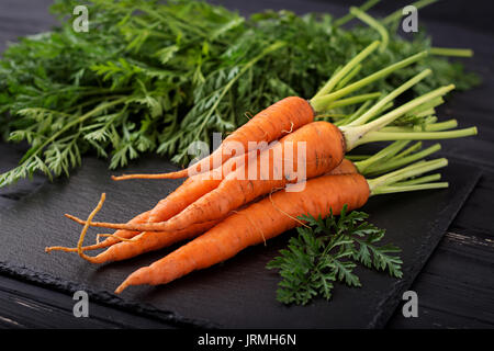 Bunch of fresh carrots with green leaves on  dark  wooden background. - Stock Photo