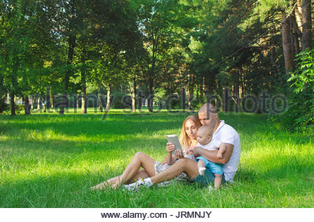 Family spending time with a tablet on nature in summer - Stock Photo