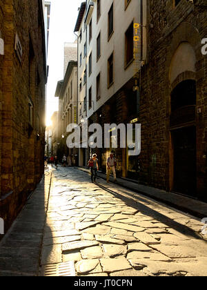 People walk on the street in Florence, Italy during sunset. - Stock Photo