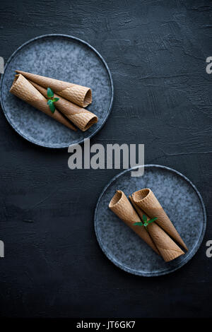 Empty ice cream cones on a plate, on a gray slate background - Stock Photo