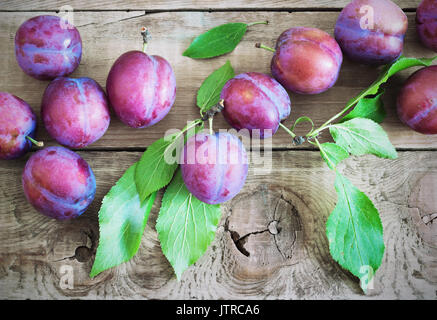 fresh purple plums on wooden rustic table - Stock Photo