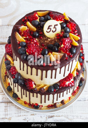 Festive twotier cake with fruit with streaks of chocolate on a