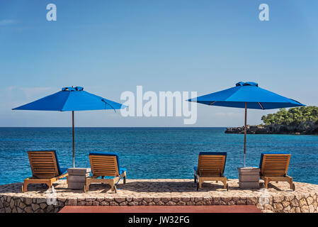 Jamaica, Negril, Beach umbrellas and lounge chairs against tranquil seascape - Stock Photo