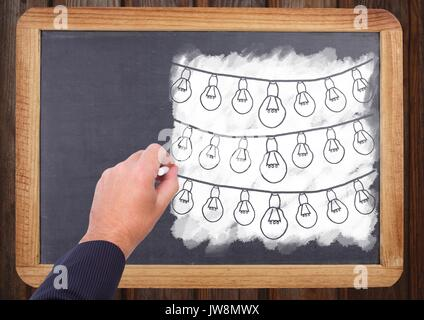 Digital composite of Hand drawing light bulbs on blackboard - Stock Photo