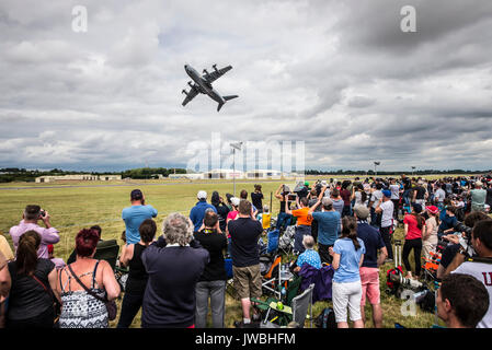 Airbus A400M Atlas military cargo plane leaping into the air to display in front of a crowd at an airshow. Space - Stock Photo