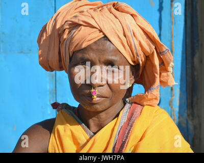 Closeup street portrait (outdoor headshot, seven-eighths view) of a mature Indian Adivasi market woman with gold - Stock Photo