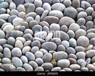 River rocks used as landscaping stones in the garden of a for Smooth stones for landscaping