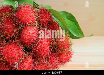 Bunch of Fresh Ripe Rambutan Fruits with Green Leaves on the Wooden Table - Stock Photo