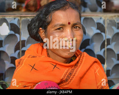 Closeup street portrait (outdoor headshot, three-quarter view) of a mature Indian Adivasi market woman with two - Stock Photo