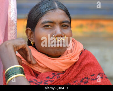Closeup street portrait (outdoor headshot, three-quarter view) of a young Indian Adivasi market woman with three - Stock Photo