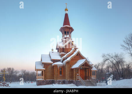 Wooden orthodox christian temple exterior in winter in forest. - Stock Photo