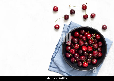 Sweet cherries in black bowl on bright grey background. Flat lay top view - Stock Photo