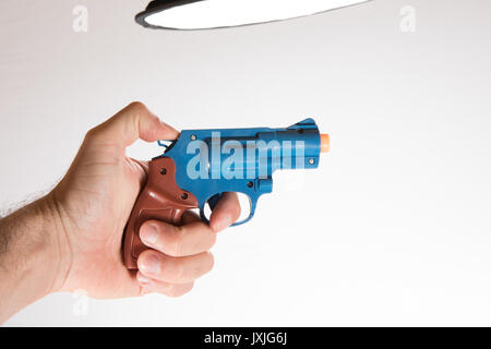 Human hand holding toy pistol against white background - Stock Photo