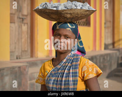 Closeup street portrait of a sari-clad young Indian Adivasi tribal woman, balancing on her head a metal bowl with - Stock Photo