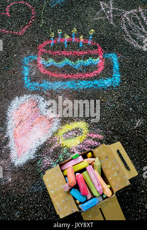 Child's colorful chalk artwork and chalk on dark asphalt. - Stock Photo