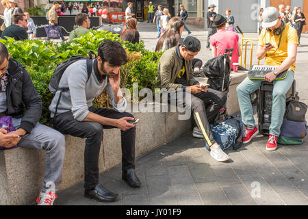 Young men looking at their mobile phones in Leicester Square, London, UK. - Stock Photo