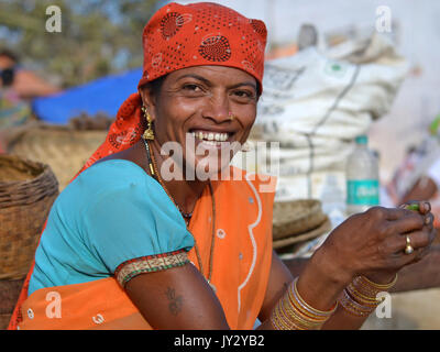 Closeup street portrait of a smiling mature Indian Adivasi market woman, peeling vegetable with both hands. - Stock Photo