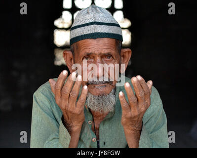 Closeup street portrait of an old Indian Muslim man with lived-in face, wearing an Islamic prayer cap (taqiyah) - Stock Photo