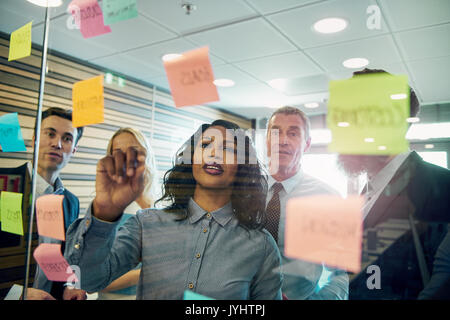 Group of businesspeople brainstorming with woman in foreground, putting sticky note on glass - Stock Photo