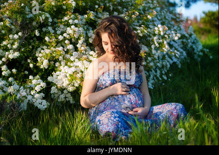 Beautiful pregnant woman with dog in green sunny nature for Gardening 3rd trimester