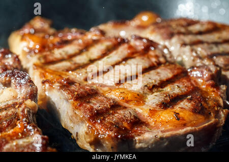 Raw Ribeye Steak with Herbs and Spices, frying on grill pan. - Stock Photo