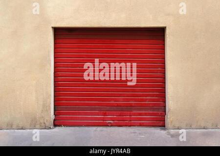 Closed red garage metal roller door exterior - Stock Photo