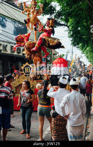 Kuta, Indonesia - March 08, 2016:  People watch the Ogoh-ogoh statues at the parade on the eve of Nyepi day on March - Stock Photo