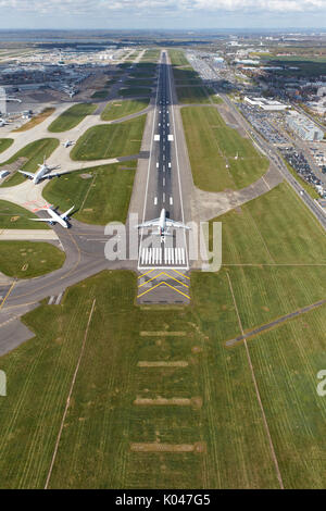 An aerial view of an aircraft preparing for takeoff on runway 27R at London Heathrow Airport - Stock Photo
