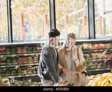 Smiling young couple grocery shopping, holding pineapple in market - Stock Photo