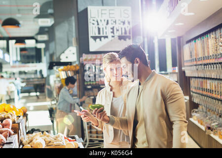 Young couple grocery shopping in market - Stock Photo