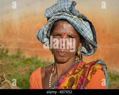 Middle-aged Indian Adivasi market woman with precious golden drop earrings. - Stock Photo
