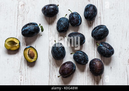 Blue plums close-up on a white wooden background - Stock Photo
