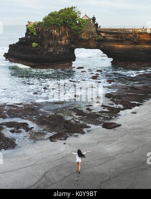 Happy woman running by empty Batu Bolong beach near holy balinese temple Tanah Lot. Nobody around in the morning. - Stock Photo