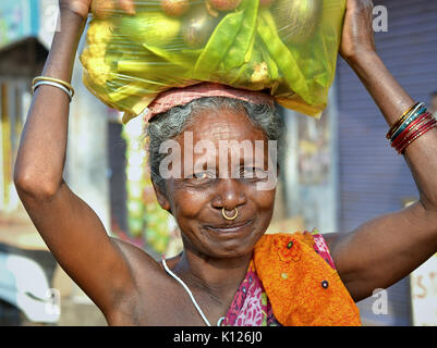 Elderly Indian Adivasi woman (Orissan tribal woman) with one golden nose ring, carrying on her head a heavy plastic - Stock Photo