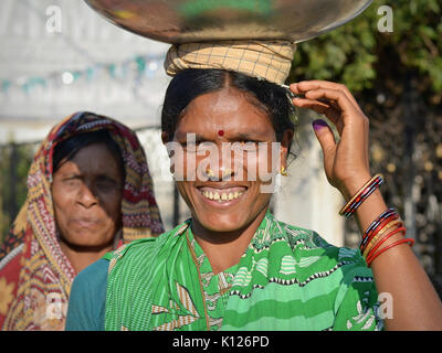 Middle-aged Indian Adivasi woman (Orissan tribal woman) with two distinctive golden nose studs, balancing  on her - Stock Photo