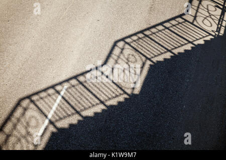 Railing shadow pattern on an empty road asphalt. Simple industrial background - Stock Photo