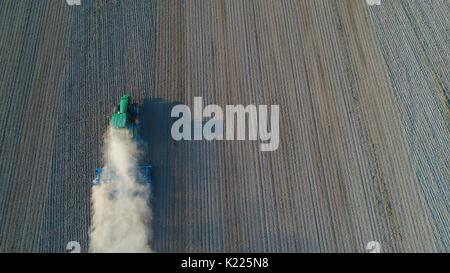 Aerial view on tractor ploughing field. Summer farm works - Stock Photo