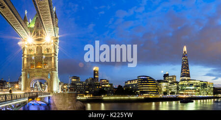 UK, London, Panoramic view of Tower Bridge and the city skyline across South of River Thames, lit up at night - Stock Photo