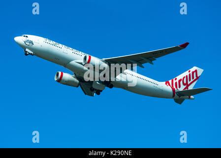 Virgin Australia passenger airplane taking off from Sydney International Airport, New South Wales, Australia. - Stock Photo