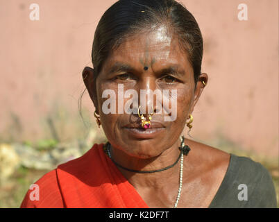 Mature Indian Adivasi market woman (Desia Kondh tribe aka Kuvi Kondh) with a tattoo on her forehead and gold-and - Stock Photo