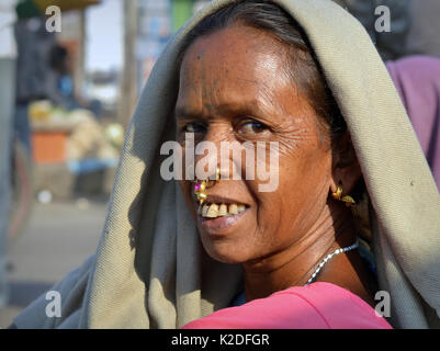 Elderly Indian Adivasi market woman (Desia Kondh tribe aka Kuvi Kondh) with gold-and-gemstone tribal nose jewellery - Stock Photo