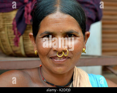 Middle-aged Indian Adivasi woman (Mali tribe) with two golden nose rings and distinctive tribal earrings - Stock Photo