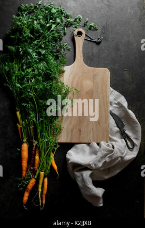 Fresh carrots on a dark background with chopping board - Stock Photo