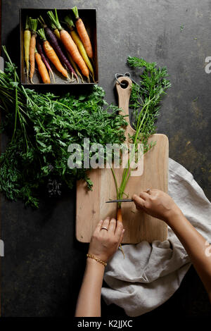 Fresh carrots on a dark background with chopping board and womans hands preparing - Stock Photo