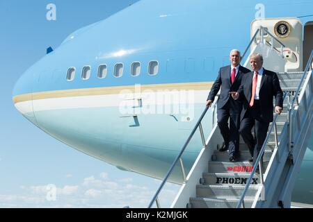 U.S. President Donald Trump and Vice President Mike Pence walk down the stairs from Air Force One on arrival for - Stock Photo